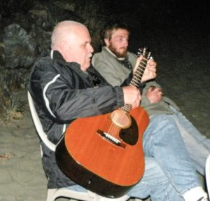 Dan Mornar playing music on the beach in Tofino